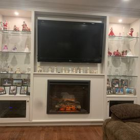 view of a fireplace with TV and display cabinets